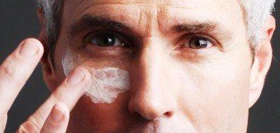 Mengoleskan krim pada kulit wajah pria