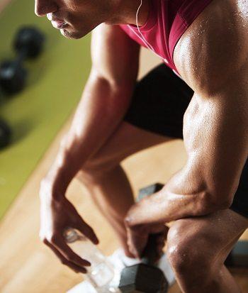 Healthy man lifting weights at a gym.