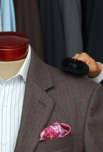cleaning men suit jacket shoulder with a brush