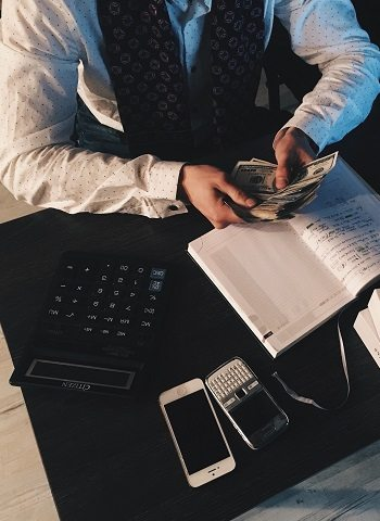 A professionally dressed man counting his money at his desk