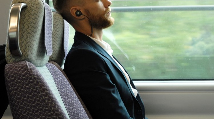 man wearing earbuds in train