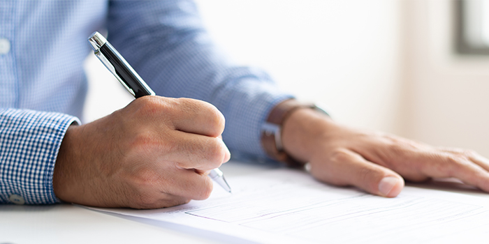 man writing on a paper