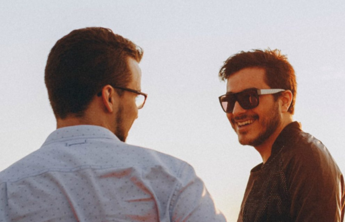 two men with sunglasses talking