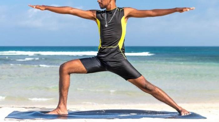 man practicing yoga on beach