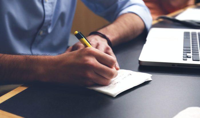 man writing list