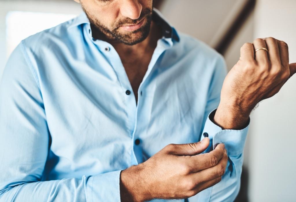 homem abotoando os punhos da camisa como se vestir bem como um homem