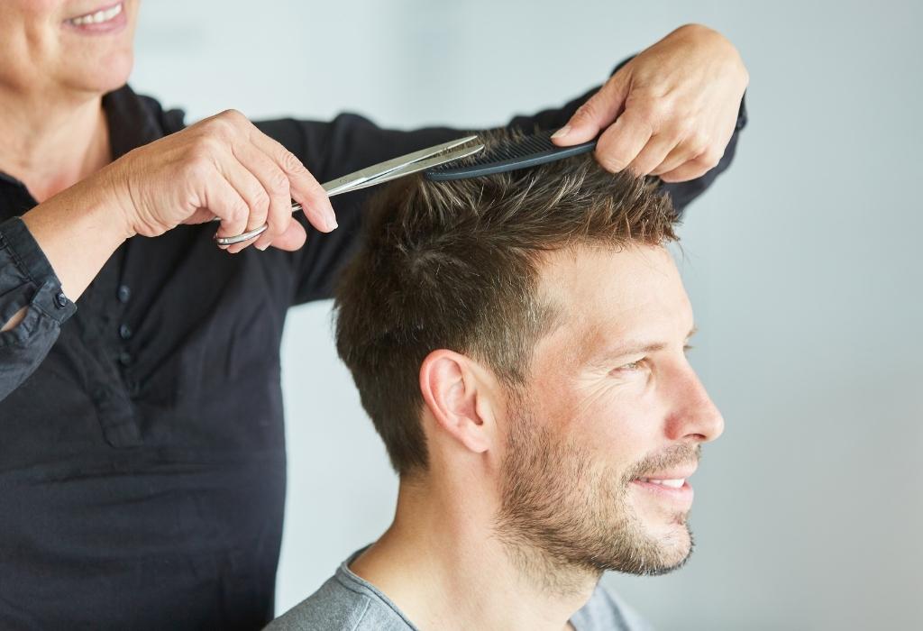 mulher corta cabelo de homem com tesoura