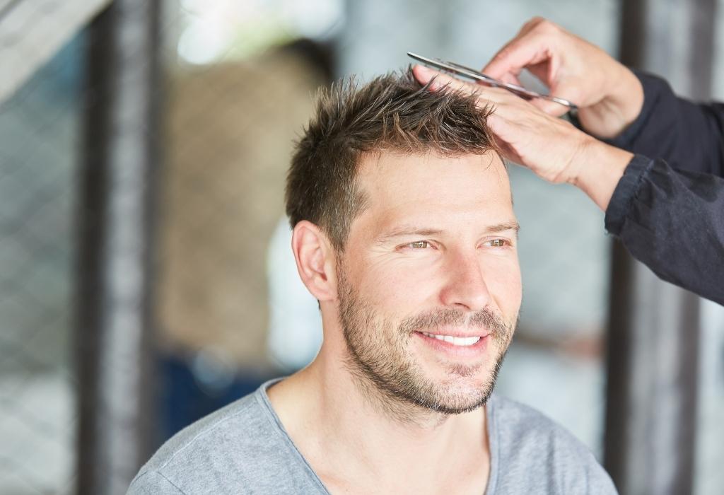 homem cortando cabelo em casa com uma tesoura