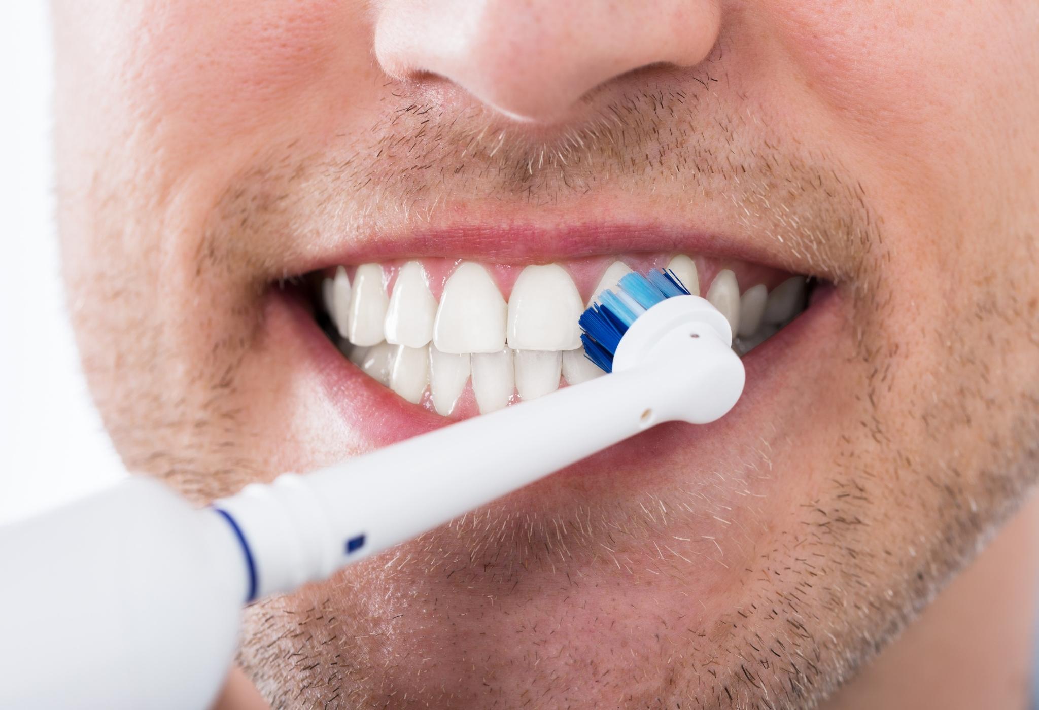 homem escovando os dentes com escova elétrica
